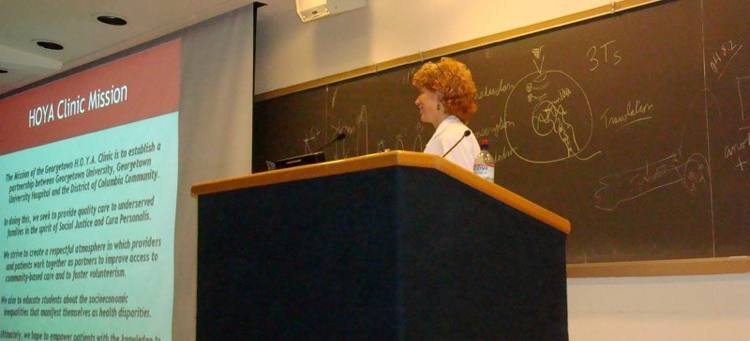 A medical school doctor lecturing in front of a blackboard.