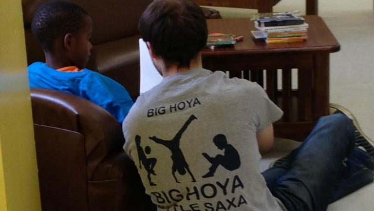 A male student displays the back of his Big Hoya Little Saxa t-shirt
